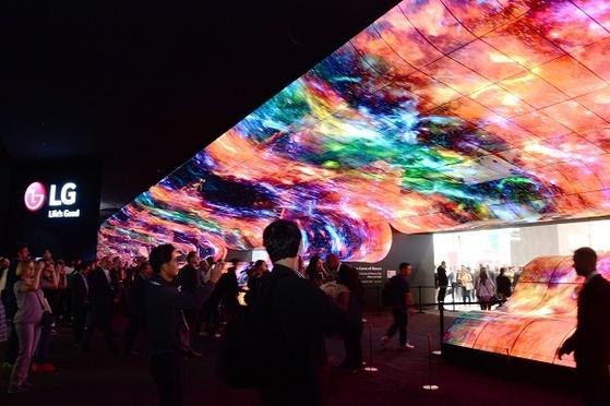 올 9월 독일 베를린에서 열린 'IFA 2019'에서 관람객들이 전시관 입구에 조성된 '올레드 폭포' 조형물의 화질을 감상하고 있다. LG의 올레드 TV는 OLED 패널을 썼기 때문에 LCD TV와 달리 돌돌 말수도 있고, 화면을 접을 수도 있다.