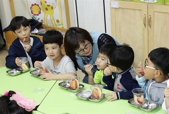 충북 영동초등학교 돌봄교실에서 아이들과 돌봄 교사가 과일 간식을 나눠먹는 시간을 갖고 있다. [사진 농림축산식품부]