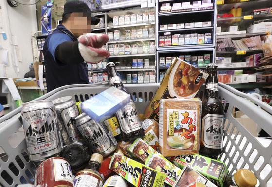 지난 7월 서울의 한 마트에서 직원이 일본 맥주, 담배, 식품들을 진열대에서 빼내 반품 준비를 하고 있다. [연합뉴스]