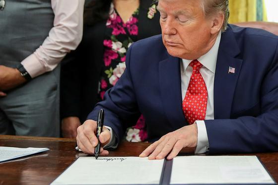 도널드 트럼프 미국 대통령이 26일 백악관에서 인디언 원주민 관련 법안에 서명하고 있다. 다음날인 27일 트럼프는 홍콩 인권법안에 서명했다. [로이터=연합뉴스]