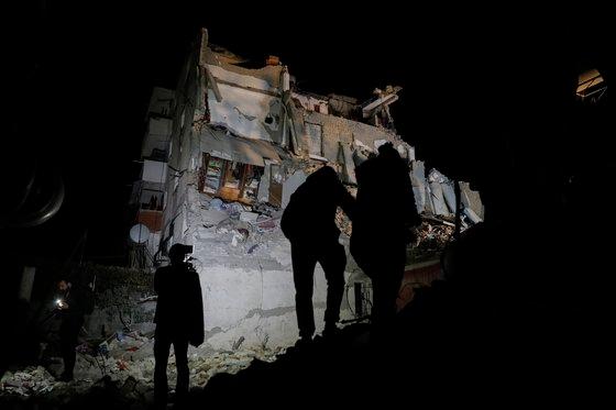 26일(현지시간) 규모 6.4의 강진이 발생한 발칸반도 알바니아에서 주민들이 무너진 아파트 건물 앞에 좌절한 채 서있다. [AP=연합뉴스]
