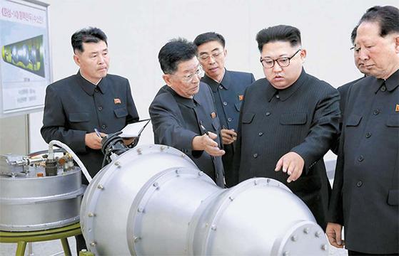 김정은 북한 국무위원장이 핵무기 병기화 사업을 현지 지도했다며 조선중앙통신이 2017년 9월 3일 공개한 사진. 장구 형태의 핵폭발장치로 보이는 물체가 있다. 왼쪽 위엔 '<화성-14>형 핵탄두(수소탄)'라고 쓰인 도면이 보인다. [조선중앙통신]