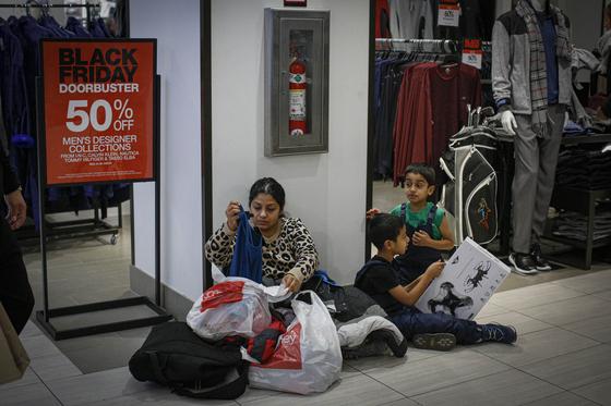 28일 미국 뉴욕의 메이시백화점 앞에서 한 가족이 구매 물품을 정리하고 있다. [AFP=연합뉴스]