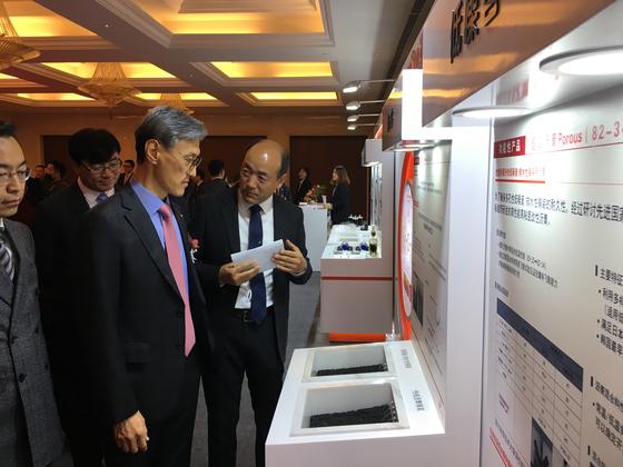 29일 중국 항저우에서 열린 '보영-SK' 현판식에서 조경목 SK에너지 사장이 제품에 대한 설명을 듣고 있다. [사진 SK이노베이션]