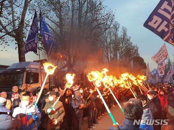 민중대회 참가자들이 서울 종로구 청와대 앞에서 횃불을 켜고 있다. [뉴시스]