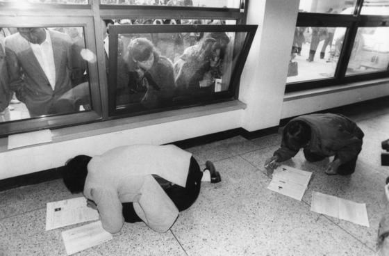 89년 11월 24일 90학년도 대입원서 접수 마감 5분을 남기고 마지막까지 눈치를 보던 수험생 2명이 접수창구 바닥에 엎드려 지망학과를 정정하느라 여념이 없다. [중앙포토]
