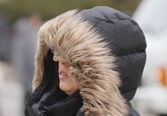 중부지방에 아침 기온이 영하권으로 떨어진 지난달 25일 오전 서울 종로구 광화문 네거리에서 한 시민이 털 달린 패딩 모자를 쓴 채 발걸음을 옮기고 있다. [연합뉴스]
