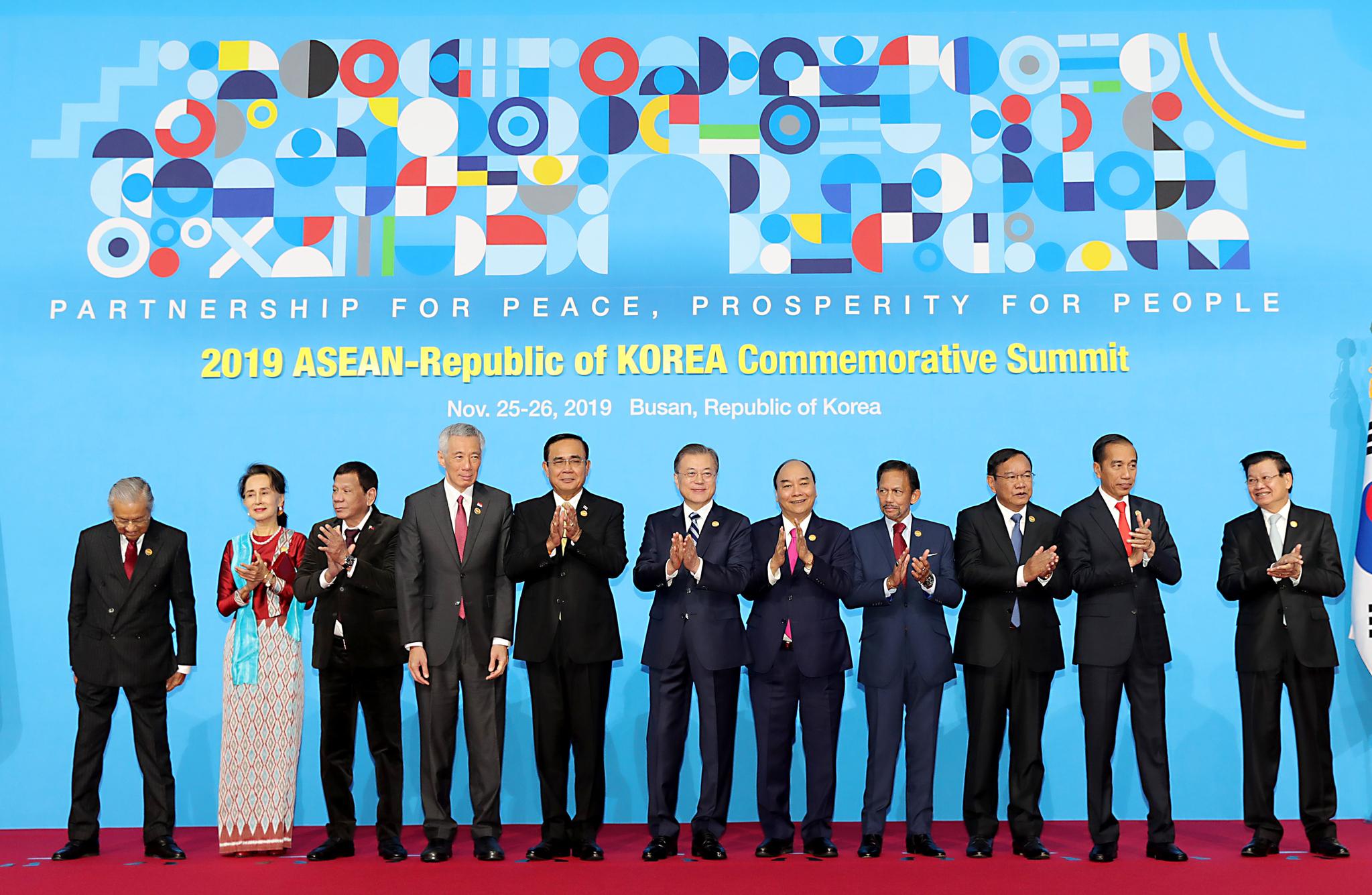 문재인 대통령이 11월 26일 오전 부산 벡스코에서 열린 2019 한-아세안 특별정상회의에서 참석자들과 기념촬영을 한 뒤 박수치고 있다. 왼쪽부터 마하티르 모하마드 말레이시아 총리, 아웅산 수치 미얀마 국가고문, 로드리고 두테르테 필리핀 대통령, 리센룽 싱가포르 총리, 쁘라윳 짠오차 태국 총리, 문 대통령, 응우옌 쑤언 푹 베트남 총리, 하사날 볼키아 브루나이 국왕, 쁘락 소콘 캄보디아 부총리 겸 외교부 장관, 조코 위도도 인도네시아 대통령, 통룬 시술릿 라오스 총리. [사진 2019 한-아세안 특별정상회의]