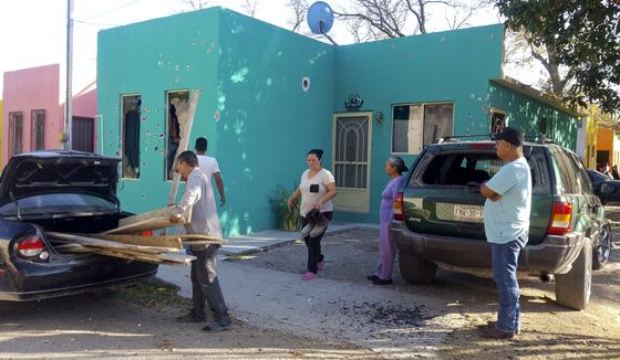 주민들이 총격을 받은 주택을 정리하고 있다. [AP=연합뉴스]