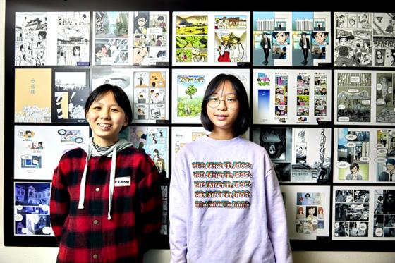 홍예린·은다민 학생기자가 다양한 만화가 전시된 벽면을 배경으로 포즈를 취했다.