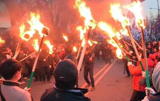 지난달 30일 오후 서울 광화문광장에서 열린 2019 전국민중대회에서 참가자들이 청와대 분수대 방향으로 행진하다 횃불을 들고 있다. [연합뉴스]