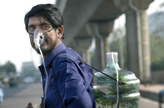 판카즈 쿠마르가 지난 1일 인도 뉴델리 인근의 노이다 지역에서 직접 만든 산소통을 짊어지고 환경 캠페인을 벌이고 있다.[신화통신=연합뉴스]