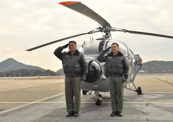 12월 3일 해군 목포기지에서 마지막 비행을 마친 알루에트-Ⅲ 조종사들이 헬기 앞에서 경례를 하고 있다. [사진 해군]