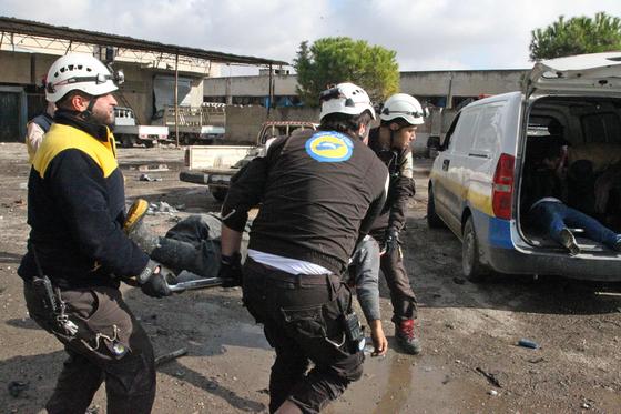 2일(현지시간) 시리아 북서부 이들립주 마아렛 알누만 시장에서 시리아 정부군 공습으로 다친 민간인을 시리아 반군 구조대원들이 앰뷸런스로 옮기고 있다. [AFP=연합뉴스]