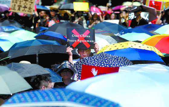 대만 총통선거가 한달 남짓 앞으로 다가왔다. 대만 유권자들 사이에 '일국양제'의 약속이 지켜지지 않은 것이 홍콩 장기 시위 사태의 원인이란 인식이 확산되면서 열세를 면치 못하던 민진당 차이잉원의 지지율이 급상승했다. 사진은 지난 6월 대만 입법원 앞에서 '하나의 중국'에 반대하는 팻말을 들고 홍콩 시위를 지지하고 있는 대만 시위대의 모습. [타이베이 AP=연합뉴스]