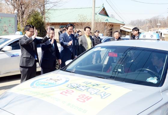 최종환 파주시장(왼쪽) 등이 지난 1일 '천원택시' 첫 이용객에게 손을 흔들며 마중하고 있다. [사진 파주시]