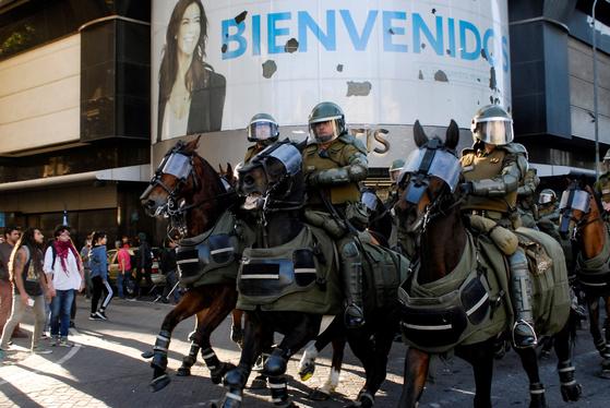 고글(?)과 다리 보호대, 방호복을 착용한 칠에 경찰 기마대. 중무장한 기마 경찰이 2일 (현지시간) 칠레 산티아고에서 시위대를 해산시키고 있다. [로이터=연합뉴스]