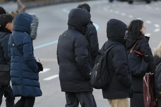 올겨울 들어 서울 낮 최고기온이 처음으로 영하권에 머물 것으로 예상되는 5일 오전 서울 광화문 거리에서 시민들이 두터운 옷차림으로 추위 피해 발걸음을 재촉하고 있다. [연합뉴스]
