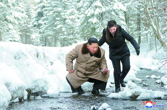 이설주가 김 위원장 어깨를 짚고 개울을 건너고 있다. [연합뉴스]