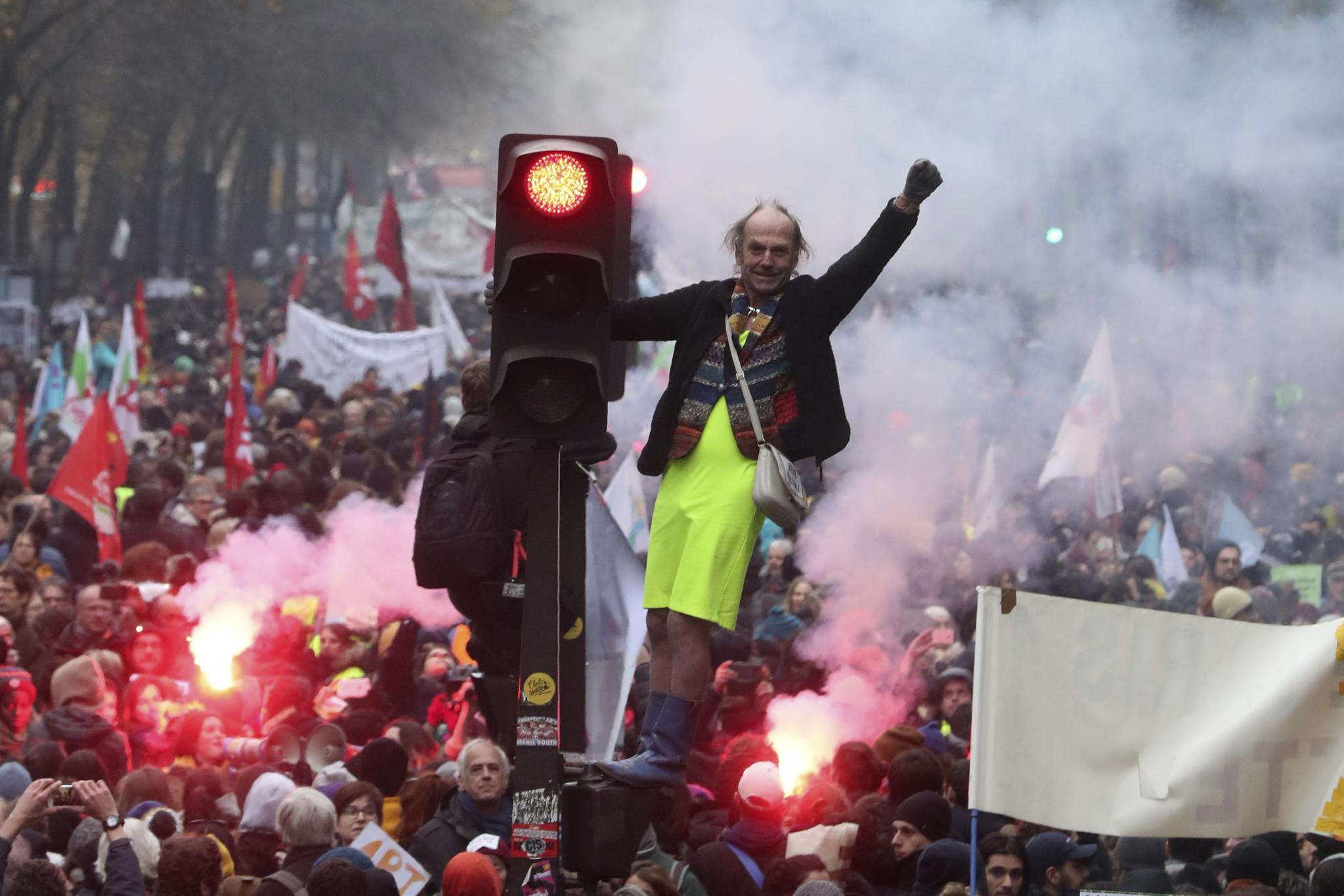 한 시위자가 5일(현지시간) 프랑스 파리에서 열린 연금개편 반대 집회에 참가해 교통신호등 위에 서 있다. [AP=연합뉴스]
