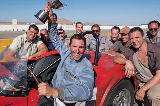실제 자동차 경기장 사진이 아니라 영화 '포드 V 페라리' 한 장면이다. 가운데 우승컵을 치켜든 사내가 주인공인1960년대 레이서 켄 마일스다. 배우 크리스찬 베일이 실존 인물과 싱크로율 높은 열연을 펼쳤다. [사진 월트디즈니 컴퍼니코리아]