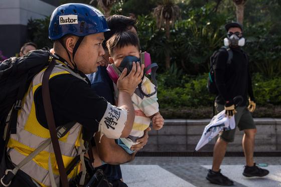 지난 10월 말 홍콩 침사추이 시내에서 한 홍콩 시민이 경찰이 쏜 최루가스로 부터 아이를 보호하기 위해 자신이 쓰던 방독마스크를 아이에게 씌워주고 있다.[AFP=연합뉴스]