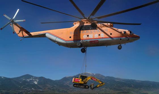 중국의 초대형 헬기가 지난 5일(현지시간) 쓰촨성 양산지족자치주 시골 마을로 건설 중기를 실어 나르고 있다. [신화=연합뉴스]