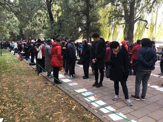 중국의 일부 공원에 가면 특정 시간을 정해 자식의 인연을 찾는 곳인 '샹친쟈오'가 있다. 지난 11월의 한 일요일 낮에 쌀쌀한 날씨에도 불구하고 많은 사람들이 자금성 옆 중산공원의 샹친쟈오에 나와 종이에 적힌 결혼 적령기 남녀의 소개서를 살피고 있다. [유상철 기자]