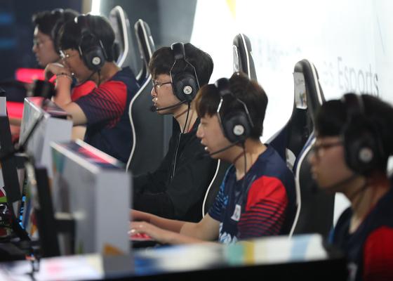 지난해 인도네시아 자카르타 브리타마 아레나에서 열린 2018 자카르타-팔렘방 아시안게임 e스포츠 리그오브레전드에 출전한 한국 선수들이 중국을 상대로 경기를 펼치고 있다.  [연합뉴스]