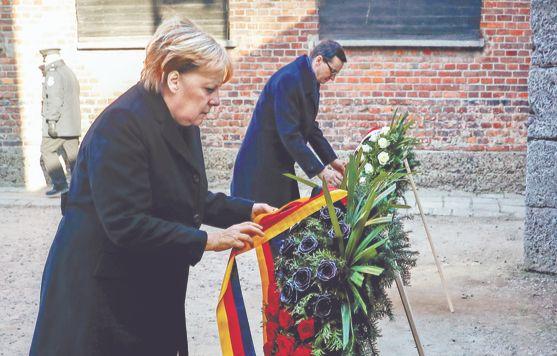 앙겔라 메르켈 독일 총리(왼쪽)가 6일(현지시각) 나치 독일이 2차 세계대전 당시 폴란드에 세웠던 아우슈비츠 강제수용소의 '죽음의 벽' 앞에서 헌화하고 있다. 마테우시 모라비에츠키 폴란드 총리가 함께했다. [로이터=연합뉴스]