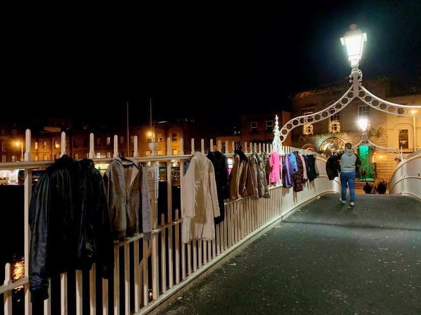 노숙자들을 위한 의복들이 줄지어 걸려있는 아일랜드 더블린의 하페니 다리에서 한 시민이 의복을 걸고 있다. [사진 트위터]