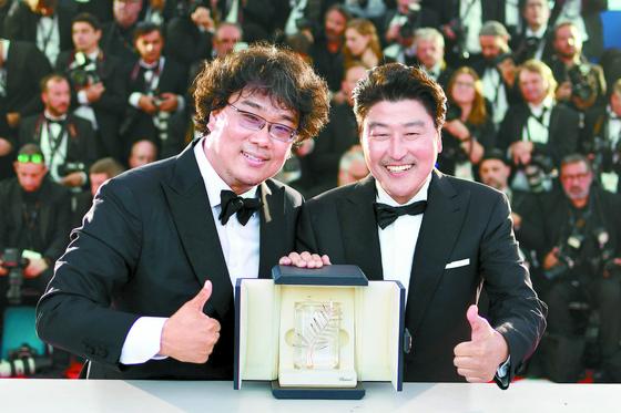 봉준호 감독(왼쪽)의 '기생충'이 또 다시 한국영화의 역사를 새로 썼다. 사진은 지난 5월 25일(현지시간) 폐막한 올해 제72회 칸영화제에서 '기생충'으로 한국영화 최초 황금종려상을 받았을 때다. 주연배우 송강호(오른쪽)와 함께 스포트라이트를 받았다. 한[AFP=연합]
