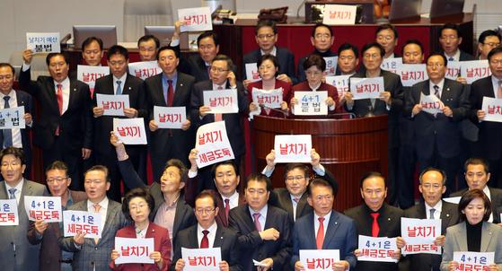 자유한국당 의원들이 10일 국회 본회의장에서 내년도 예산안 통과에 대해 반발하는 피켓 시위를 하고 있다. 김경록 기자
