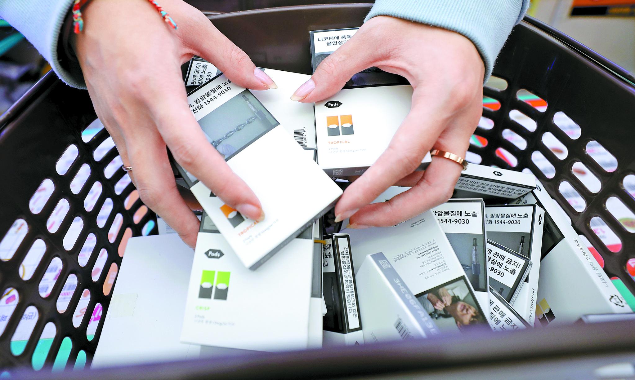 지난 10월 서울 시내 편의점 GS25에서 점원이 판매중단된 가향 액상형 전자담배를 수거하고 있다. [연합뉴스]