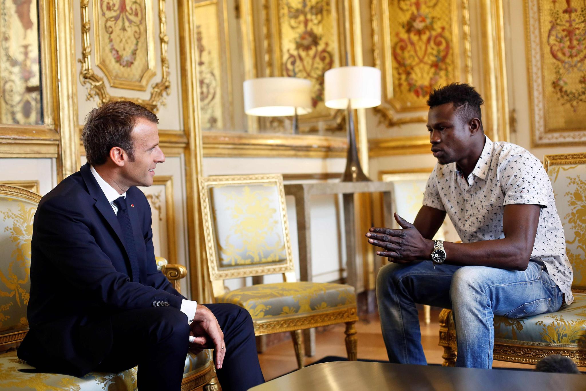 프랑스 파리 아파트 5층 발코니에 매달린 네 살 아이를 맨손으로 구출한 말리 출신의 마무두 가사마(오른쪽)가 지난 5월 28일 대통령 궁에서 에마뉘엘 마크롱 프랑스 대통령을 만나고 있다. [AFP=연합뉴스]