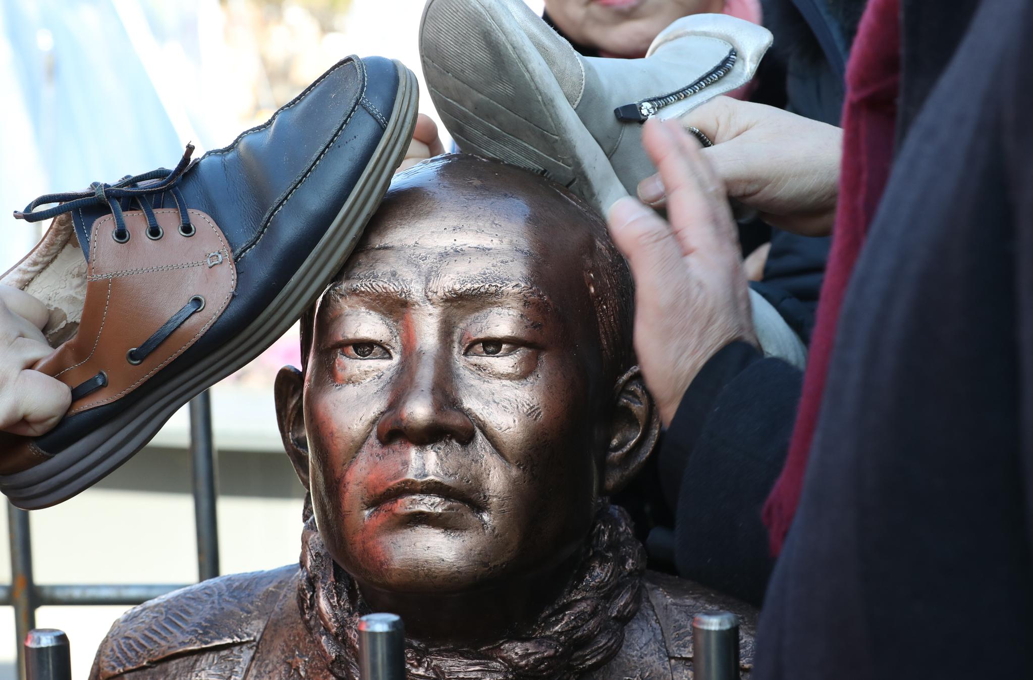 신군부가 일으킨 12·12 군사반란 40주년인 12일 5.18 관련 단체 회원들이 서울 광화문광장에서 전두환 전 대통령의 구속 수사를 촉구하는 기자회견을 한 뒤 이를 상징적으로 표현하기 위해 제작한 동상 조형물을 때리는 퍼포먼스를 하고 있다. [연합뉴스]