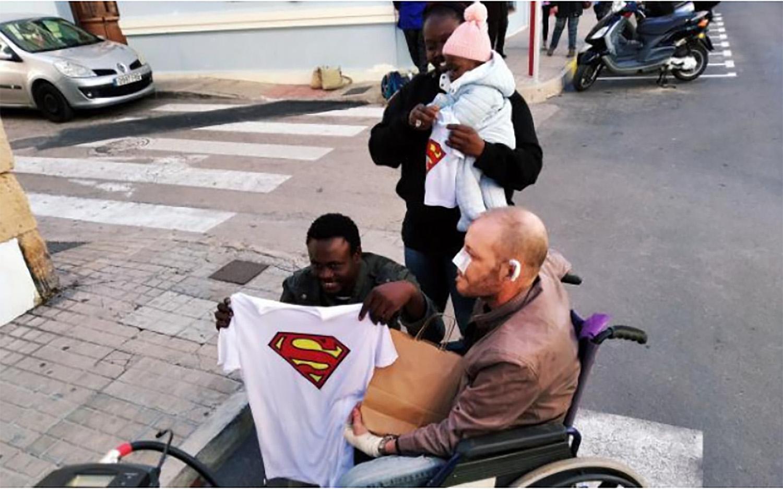 고르기 라민 소우(왼쪽)가 9일(현지시간) 그가 구한 카우델리로부터 슈퍼맨 티셔츠를 선물받고 있다. [사진 고르기 라민 소우]