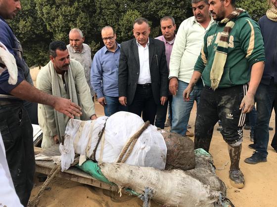 이집트 고대유물부 관계자들이 11일(현지시간) 기자 지역에서 발굴된 람세스 2세의 분홍색 화감암 동상을 옮기고 있다. [신화=연합뉴스])