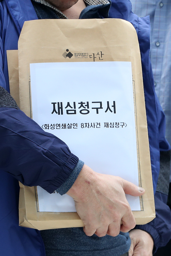 지난달 13일 화성연쇄살인 8차 사건으로 복역 후 출소한 윤모씨(52)가 재심청구서를 제출하기 위해 법원으로 이동하고 있다. [뉴스1]