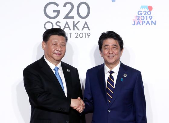 시진핑(왼쪽) 중국 국가주석이 지난 6월 28일 오전 인텍스 오사카에서 열린 G20 정상회의 공식 환영식에서 의장국인 일본 아베 신조 총리와 인사하고 있다. [청와대사진기자단]
