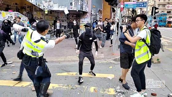 지난달 11일 홍콩 사이완호에서 홍콩 경찰관이 시위대를 향해 실탄을 발사하고 있다. [로이터=연합뉴스]