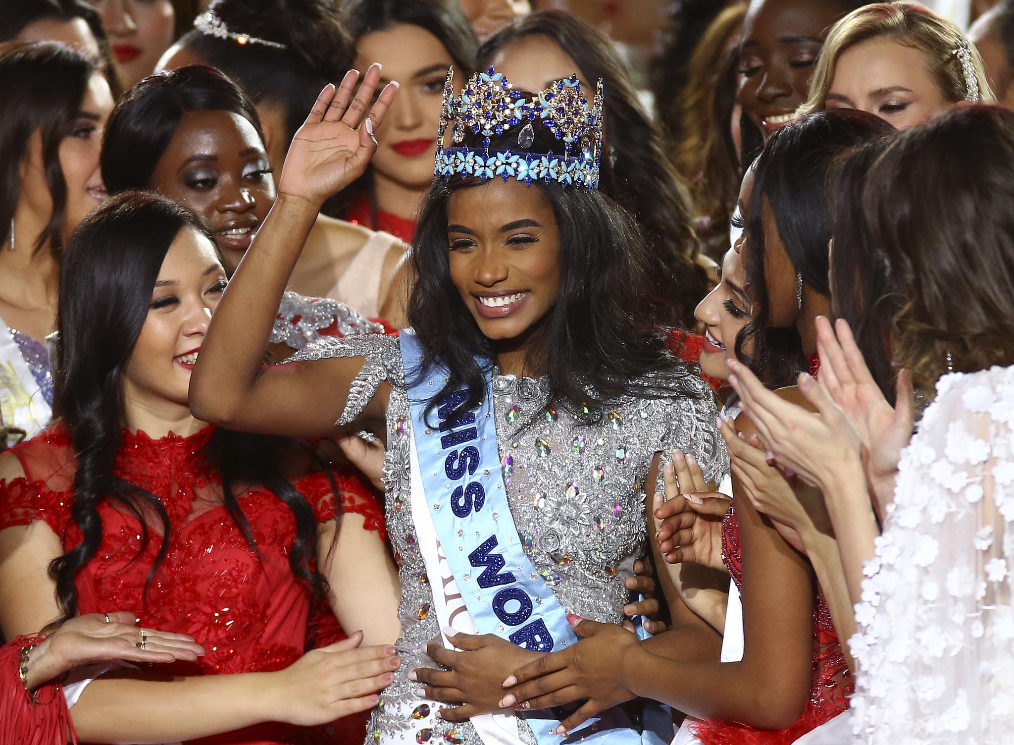 미스 자메이카 토니 안 싱이 14일(현지시간) 영국 런던의 엑셀 센터에서 열린 제69회 미스 월드 선발대회에서 2019 미스 월드로 선정된 뒤푸른색 왕관을 쓰고 다른 참가자들의 축하를 받으며 인사하고 있다. [AP=연합뉴스]