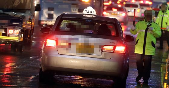 서울시 택시 삼진아웃제에 따라 택시기사가 처음으로 퇴출됐다. 사진은 경찰이 승차거부 택시를 적발하고 있는 모습. [중앙포토]