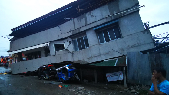 필리핀 강진으로 15일(현지시간) 파다다 시의 건물이 붕괴되면서 인근에 주차돼 있던 차량을 덮쳤다. [AFP=연합뉴스]