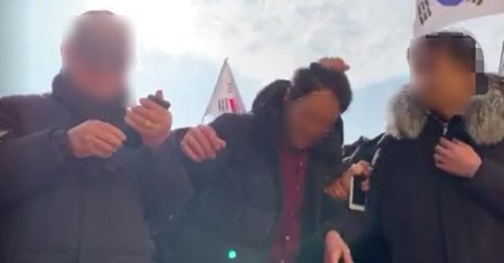 국회 앞 보수 지지자들에 의해 머리채 잡히는 정의당 관계자. [정의당 제공 영상 캡처=연합뉴스]