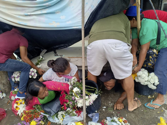 필리핀 남부 파다다 시에서 15일(현지시가) 주민들이 지진으로 붕괴된 건물에 깔린 시민들을 구조하고 있다. [AP=연합뉴스]