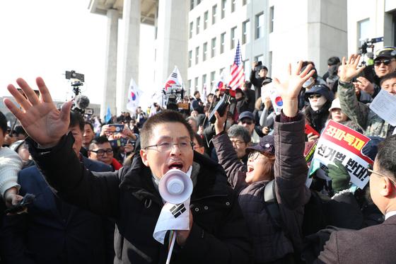 황교안 자유한국당 대표가 16일 국회에서 열린 '공수처법 선거법 날치기 저지 규탄대회' 참가자들과 함께 시위를 벌이고 있다.   이들은 본청 무단 진입을 시도하다 경찰에 막혀 입구에서 집회를 열었다. [연합뉴스]