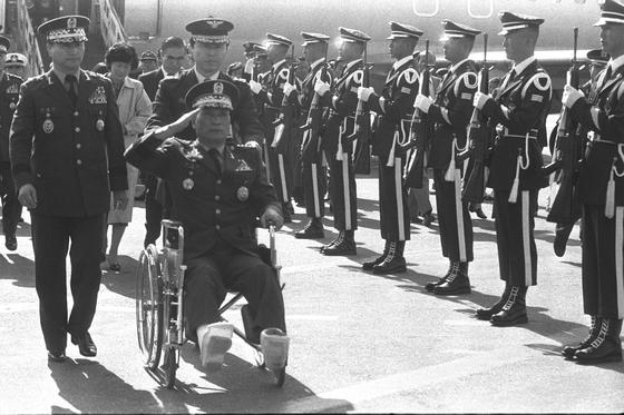 1983년 10월 아웅산 국립묘지 테러 현장에서 크게 다친 이기백 전 장관이 필리핀 클라크 공군기지 병원에서 치료받은 뒤 휠체어를 타고 귀국하고 있다. [연합뉴스]
