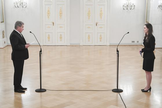 핀란드의 산나 마린 총리(오른쪽)가 지난 10일 헬싱키의 대통령 관저에서 사울리 니니스퇴 대통령 앞에서 취임 선서를 하고 있다. 간단하고 소박한 모습이 인상적이다. [EPA=연합뉴스]