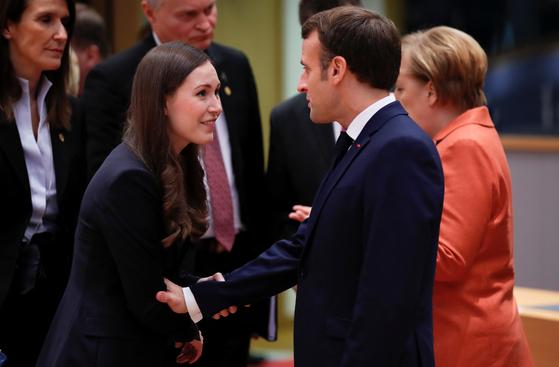 지난 12일 벨기에 브뤠셀에서 열린 유럽연합(EU) 정상회의에서 산나 마린 핀란드 총리(왼쪽)가 에마뉘엘 마크롱 프랑스 대통령을 만나고 있다. 마크롱은 만 39세이던 2017년 5월 프랑스 대통령에 올랐다. [로이터=연합뉴스]